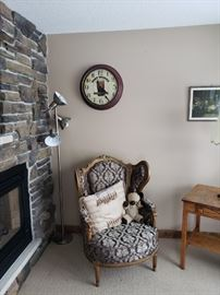 Antique wing-back chair, floor lamp, breweriana clock.
