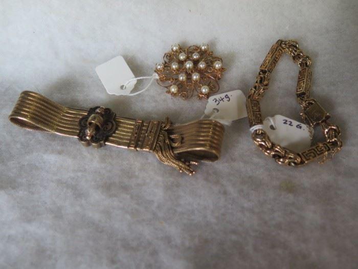 gold bracelets and brooch