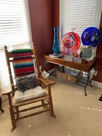 Artglass, vintage rocking chair, handwoven blanket, wooden hutch, ornate storage boxes.
