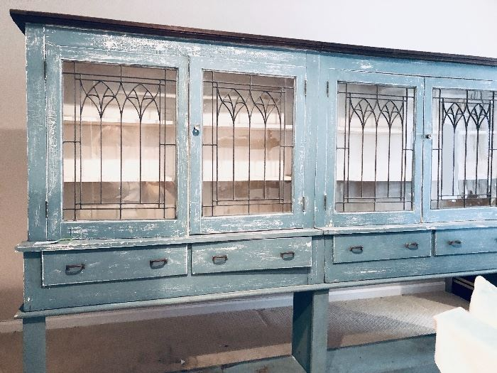 This piece disassembles. It's a French Country Sideboard used by the owner to display her collections.
