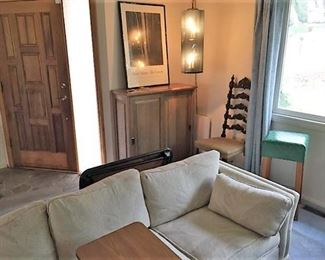 The sofa, chairs, and cabinet are all available for sale.