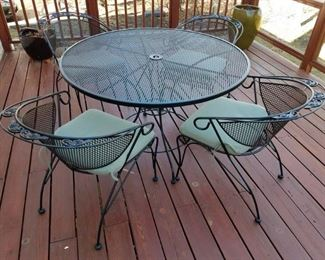 Wrought iron patio table & four chairs set with cushions.
