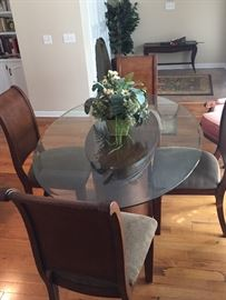 Dining room table with solid wood base and chairs (4) with upholstered seats; oval heavy glass top