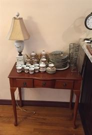 A side table with a collection of dishware on top.