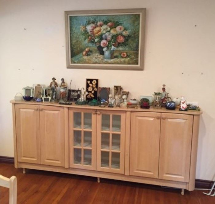 The buffet cabinet, a painting, and various other items.