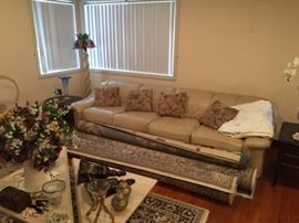 This photo shows the leather sofa, three rolled-up area rugs, and a section of the coffee table (with another area rug underneath).