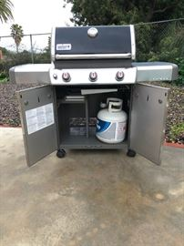 Weber Genesis gas grill on wheels with propane tank and racks included