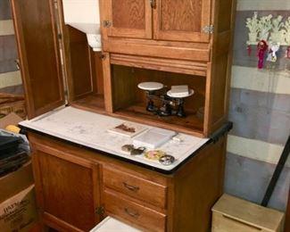 oak Hoosier (?) cupboard with porcelain top, roll door, flour sifter & bread drawer.