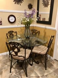 Round glass top dining table with iron base & 4 chairs - wall decor