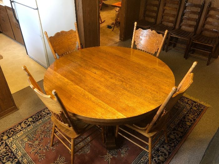 Craftsman style pedestal dining table and antique style pressed back chairs.