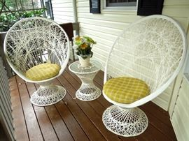 Metal wicker peacock chairs; side table and potted ceramic planter with synthetic gerber daisies and seashell beaded doily.