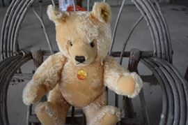 """""""Steiff"""" Teddy Bear with an original paper tag and tag in the ear. Notice also the antique tree limb child's chair."""