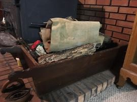 This might be hard to make out, but it is an old vintage dough box.  Bread was a staple back in the day, and the dough would be kneaded in this box.  Owner is using it for firewood next to the woodburner.
