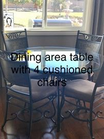 Dining area table with 4 cushioned chairs