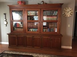 Large antique bookcase from Brazil. Base was made in the 80's, the top is much older (has wavy glass) but not sure exactly how old. Approximately 9 ft long, 7 1/2 ft tall, this is an impressive piece that gets lots of comments. Hate to let it go but I don't have a spot in my house for it. Has been modified a few times over the years to get it through doorways, etc. so it's not perfect. These mods make it possible to transport in (at least) 5 separate pieces.  $2000