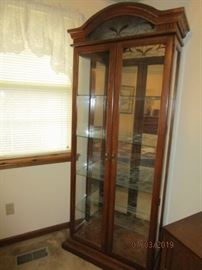 Tall curio cabinet with stained glass on the top front