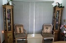 Corner lighted curio cabinets with glass shelves.  2 arm dining chairs. Tropical Palm and Pineapple throw pillows. small storage chest (appears to be faux leather/vinyl)
