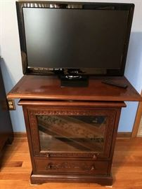 Cherry TV stand with swivel top (TV not included, sold separately). Glass door opens and slides in and storage drawer underneath for storage. Excellent condition.