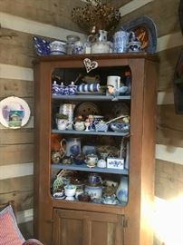 Corner cupboard filled with blue and white pottery & dishes