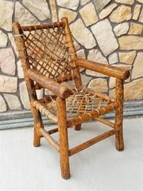 Peeled log and snowshoe weave rawhide chair from the historic Leeks Lodge in Jackson, Wyoming.