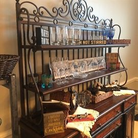 bar ware. fun signs for the home. stemware of all types on a beautiful iron and wood server or hutch