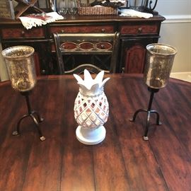 the dining table with a pineapple candle holder and iron and glass sconces
