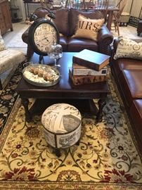 This is a fun room. The family room or den. Beautiful rug under a contemporary square coffee table. Fun decorative objects and one of two matching stools. Just a peek at the matching love seat and sofa in soft supple leather