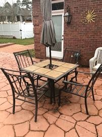 an outdoor iron table with chairs and umbrella. we have the nice like new cushions too
