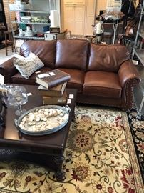 The leather sofa looks great on the area rug and with the oversized mahogany coffee table