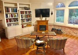 Books, Samsung flatscreen tv, electric fireplace, antique anchor base coffee table, custom upholstered chairs, stools made from antique ship pulleys