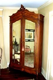 Early 1800's French armoire with mirrored doors and shelves and drawer inside.