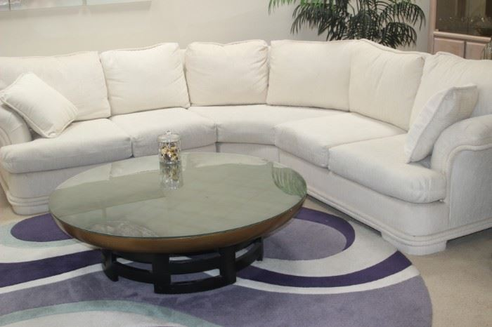 Off white fabric sectional. Asian themed round coffee table with glass top, round area rug.