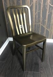 Crate and Barrel Delta Dining Chair With Brushed Brass Finish, Sculpted Seat, and Protective Foot Caps.    Contemporary, industrial, lightweight