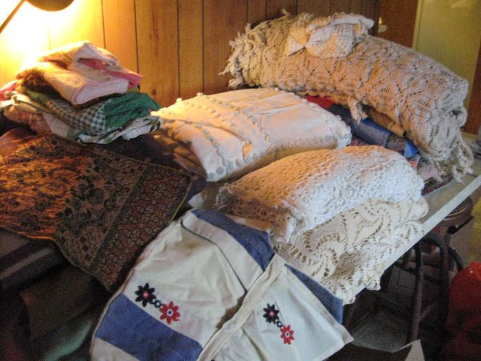 Handmade crocheted tablecloths and bedspread.  Old aprons and a vintage clothespin dress.