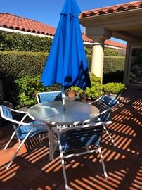 Blue and White patio table with bright blue umbrella
