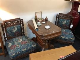 Hand carved wooden upholstered side chairs with flowers & birds. Casters on front 2 legs of both chairs. Very well made & loved  with matching table in between