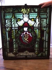 Glass window purchased from a dealer who said it came from a church in Charleston in the 1800s.  The frame is hand forged iron.   We staged a light behind the glass for this photo to showcase it's beauty.