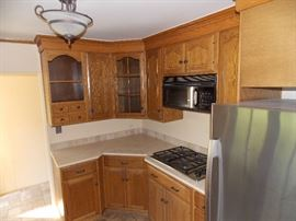 oak kitchen cabinets , stainless steel refrigerator , stainless steel cook top microwave granite counter tops dishwasher stainless steel kitchen sink