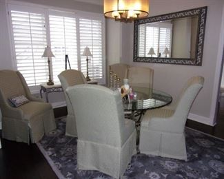 Stunning formal dining room set Glass top scalloped edge with 6 matching upholstered with pleated skirt chairs and one of 3 matching  clean area rugs.