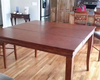 Bar height table with center pull-out leaf and 6 chairs with light gray padded seats, in excellent condition.
