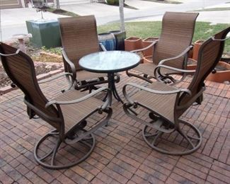 4 rocker/swivel chairs. Glass top patio table. Pottery not for sale.