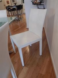 Set of six white leather dining room chairs.