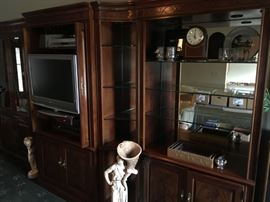 Accent door front panels,  curve side units, and recess lighting make this wall unit upscale elegant in style.