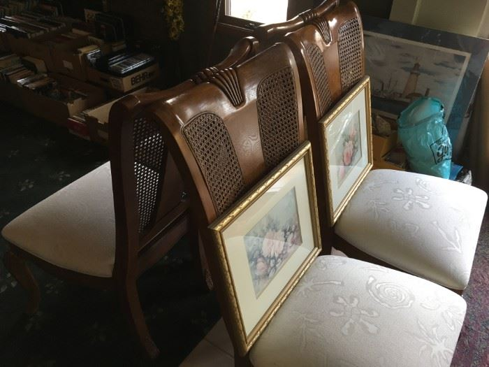 Thomasville fine wood and cane back dining chairs. With framed art work here and there.
