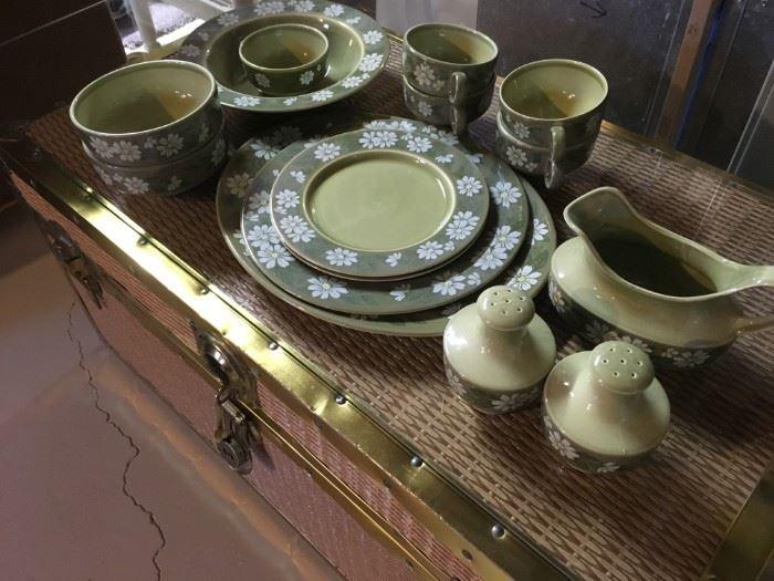 A dish set display on-top of a cedar line wicker storage chest.