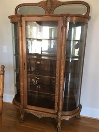 This is a beautiful antique three glass paneled cabinet with curved glass on each side, please look at the carvings on this piece!