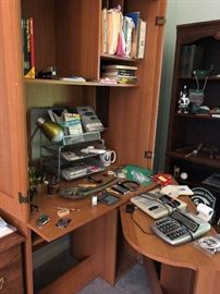 Computer hutch closes up.  Office lamp, calculator with tape and office supplies.