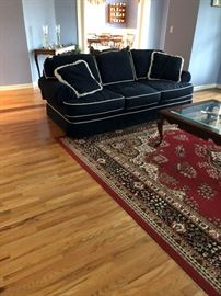 Blue cordoroy couch and large rug.