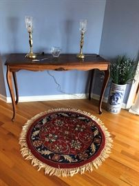 Foyer table, electric hurrican lamps and small round rug.