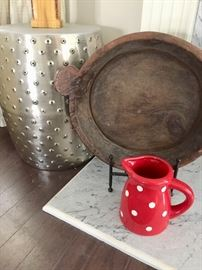 Fun silver Chinese garden seat looks lovely paired with rustic cooking pot and bright polka-dot pitcher.